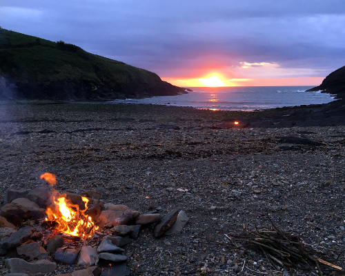 Fire on beach at sunset ready for returning coasteer